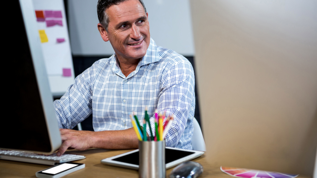 Happy man working on computer in office